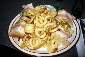 En solid porsjon med Club Sandwich og pommes frites.